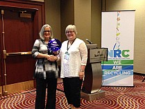 Patty Moore, Moore Recycling Associates presents Mary Ann Remolador, NERC Assistant Director, with NRC award.